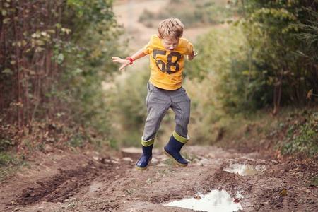 Photo pour Boy in gumboots jumps into the puddle - image libre de droit