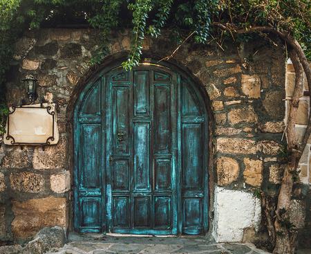 Photo pour Blue grunge wooden door in brick wall - image libre de droit