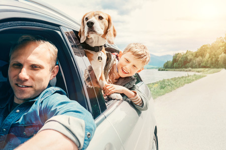 Photo pour Father with son and dog look from the car window - image libre de droit
