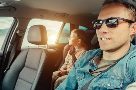 Father with son sit in car