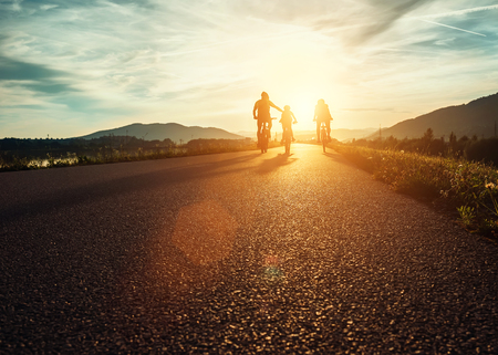 ?yclists family traveling on the road at sunset