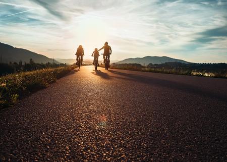 Photo pour Ð¡yclists family traveling on the road at sunset - image libre de droit