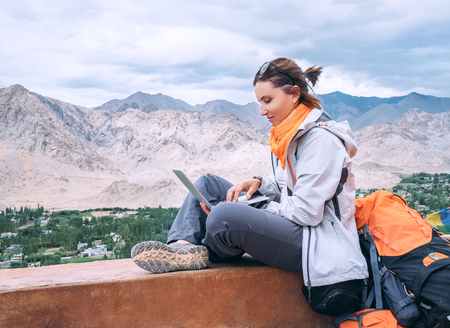 Photo for Backpacker with laptop sits on the top view point under mountain settelment - Royalty Free Image
