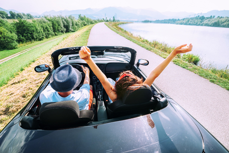 Foto de Couple in love ride in cabriolet car - Imagen libre de derechos