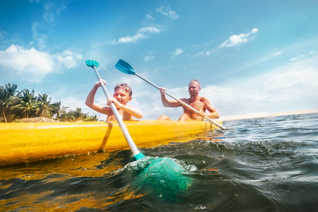 Photo pour Father and son are sailing in the canoe - image libre de droit