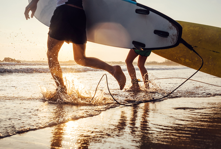 Foto de Son and father surfers run in ocean waves with long boards. Close up splashes and legs image - Imagen libre de derechos