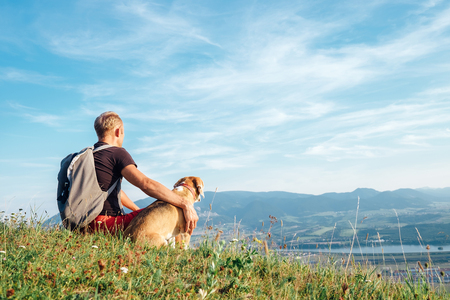 Foto de Man with his beagle dog sits on the top of hill over the mountain valley - Imagen libre de derechos