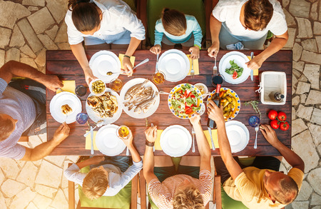 Foto de Big family have a dinner with fresh cooked meal on open garden terrace - Imagen libre de derechos