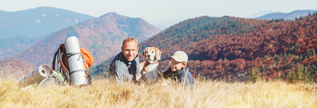 Foto de Father and son backpackers hikers rest on mountain hill with their beagle dog - Imagen libre de derechos