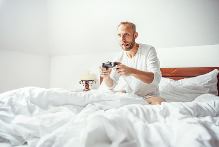 Big little boy: adult man waked up and plays PC games sitting in bed