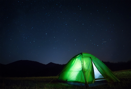 Photo for Camping tent with light inside is on the mountain valley under night starry sky - Royalty Free Image