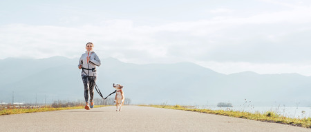 Foto de Bright sunny Morning Canicross exercises. Female runs with his beagle dog and happy smiling. - Imagen libre de derechos