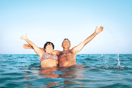Foto de A happy caucasian senior couple enjoys their sea vacation on the beach - Imagen libre de derechos