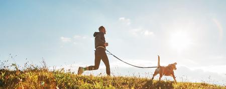 Foto de Man runs with his beagle dog at sunny morning. - Imagen libre de derechos