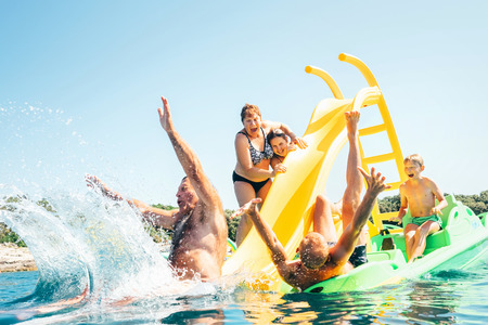 Photo pour Happy crazy family hands up on floating Playground slide Catamaran as they enjoying sea trip as they have summer season vacation - image libre de droit