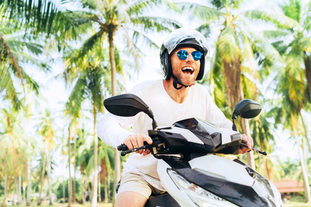 Photo pour Happy smiling and screaming male tourist in helmet and sunglasses riding motorbike scooter during his tropical vacation under palm trees - image libre de droit