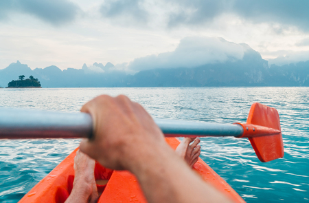 Photo pour POV of Man floating in kayak holding paddle during early morning tour. Khao Sok national park, Cheow Lan lake, Thailand - image libre de droit