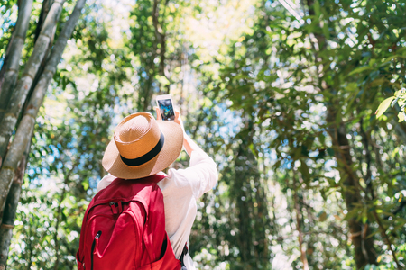 Photo for Woman with backpack on trek through jungle forest stopping taking picture with smartphone - Royalty Free Image