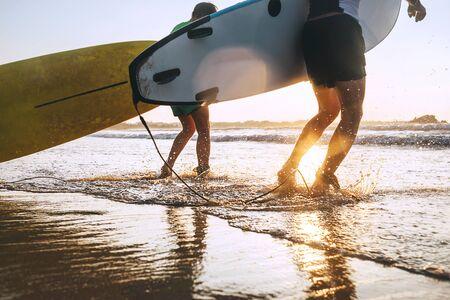 Foto de Son and father surfers run in ocean waves with surfing boards - Imagen libre de derechos