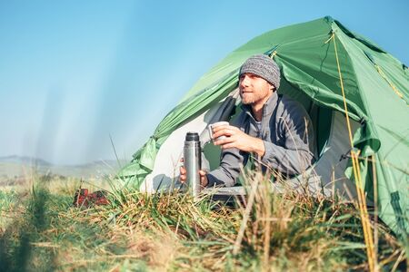 Man traveler waked up in tent and drinks hot tea