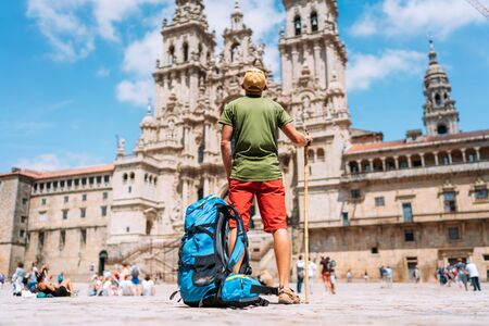 Photo for Young backpacker man pilgrim standing on the Obradeiro square (plaza) - the main square in Santiago de Compostela as a end of his Camino de Santiago pilgrimage. - Royalty Free Image