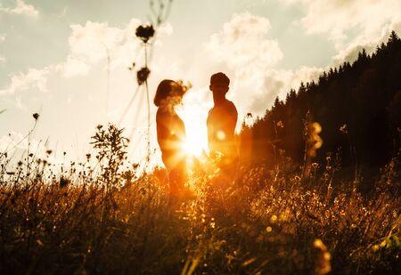 Foto de In love couple silhouets among high grass on sunset meadow - Imagen libre de derechos
