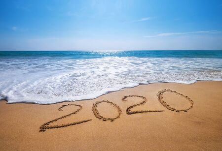Photo pour Happy New Year 2020 is coming concept sandy tropical ocean beach lettering. - image libre de droit