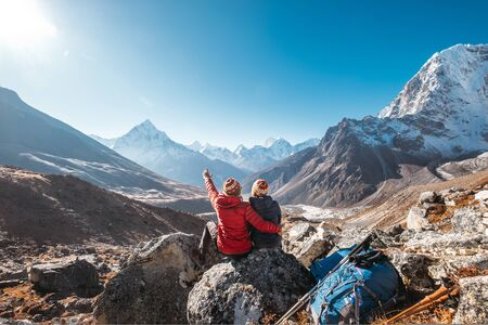 Photo pour Couple having a rest on Everest Base Camp trekking route near Dughla 4620m. - image libre de droit