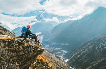 Photo for Young hiker backpacker female sitting on the cliff edge and enjoying Ama Dablam 6,812m peak view - Royalty Free Image