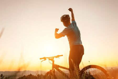 Photo pour Man biker man meets a sunset in top of hill. He rising a one arm greeting on another successful day ending. Active sport people concept image - image libre de droit