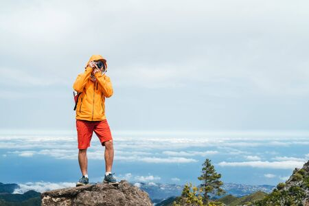 Photo pour Young adult caucasian man dressed sporty clothes with backpack taking a picture from Pico Ruivo mount 1861m - the highest peak on the Madeira Island,Portugal. Active vacation concept image. - image libre de droit