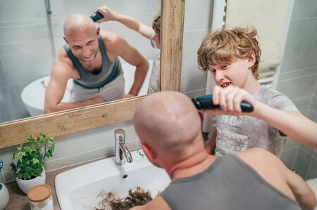 Photo pour Teenager son helping his father to trim a bald head gently using electric rechargeable Trimmer in bathroom. Funny home scene and family relatives concept image. - image libre de droit