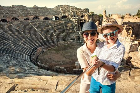 Photo pour Mother with son smiling to camera taking a selfie photo in antique theatre using a selfie stick. Traveling around the world with kids concept image. - image libre de droit