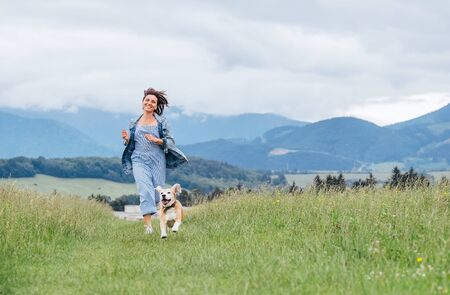 Photo pour Happy smiling running beagle dog portrait with tongue out and owner female jogging by the mounting meadow grass path. Walking in nature with pets, happy healthy active people lifestyle concept image. - image libre de droit