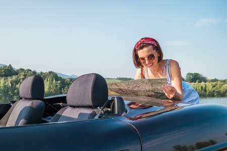 Photo pour Happy sincerely smiling woman looking a right road in the roadmap during her auto travel in the convertable cabriolet car. Traveling and navigation concept image. - image libre de droit