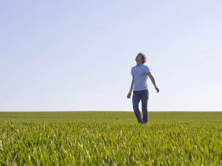 Photo for boy teenager walking on a field covered with green shoots of wheat - Royalty Free Image