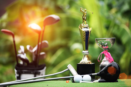 Photo for Collection of golf equipment resting on green grass with green background - Royalty Free Image