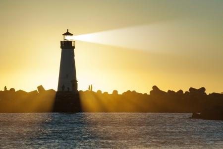 Lighthouse with light beam on ocean