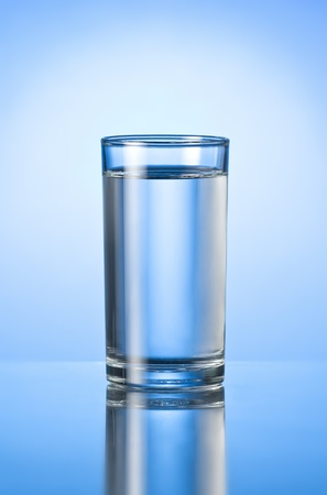 glass of pure water on blue glossy backgroundの写真素材
