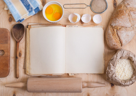 Baking light warm background with blank cook book, cutting board, eggshell, bread, flour, rolling pin. Vintage wood table from above. Rustic background with free text space.