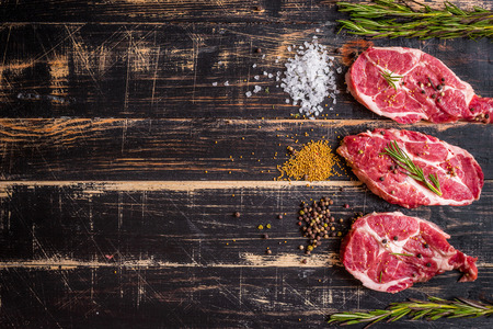 Raw juicy meat steak on dark wooden background