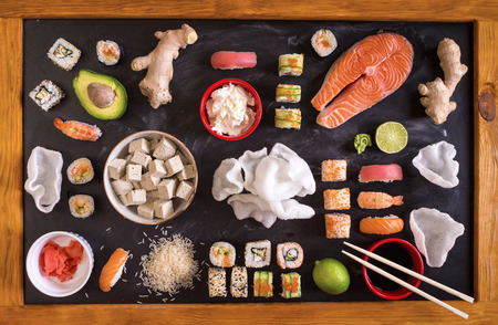 Set of traditional japanese food on a dark background. Sushi rolls, nigiri, raw salmon steak, rice, cream cheese, avocado, lime, pickled ginger (gari), raw ginger, wasabi, soy sauce, nori, �hopsticks. Asian food frame. Dinner party. Space for text