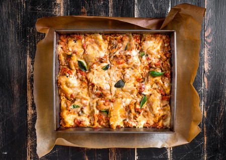 Top view of a delicious traditional italian lasagna made with minced beef bolognese sauce topped with basil leafs served on a rustic dark wooden table