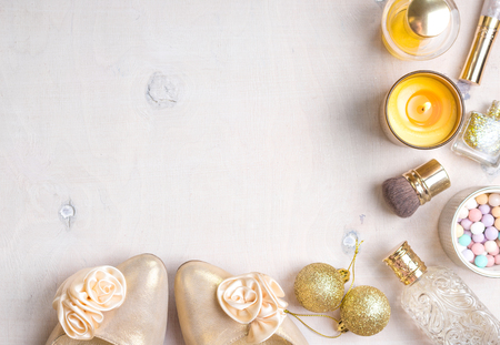 Photo pour Cosmetic objects frame with gold heels, christmas balls, gold glitter nail polish, perfume bottle, burning candles, blush, lip gloss, brushes. - image libre de droit