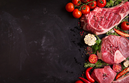 Photo for Raw juicy meat steaks ready for roasting on a black chalk board background. Rib eye steak on the bone, veal shank (ossobuco), fillet with cherry tomatoes, hot pepper and herbs. Space for text - Royalty Free Image