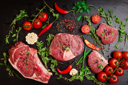 Foto de Different types of steaks set. Assorted raw meat on a black chalk board background. Rib eye steak on the bone, veal shank (ossobuco), fillet with cherry tomatoes, hot pepper and herbs. - Imagen libre de derechos