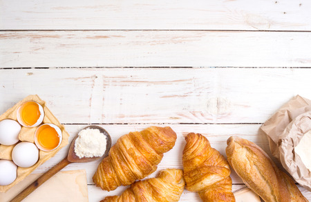 Freshly baked croissants and baguette with flour, wooden spoon, piece of paper, eggs and egg yolks in a carton tray on the white wooden table. Bakingpastry background. Free space for text