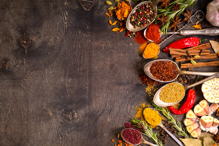 Photo pour Set of various aromatic colorful spices in old vintage spoons and herbs on a dark wooden background. Space for text. Food frame. Ingredients for cooking. Top view - image libre de droit