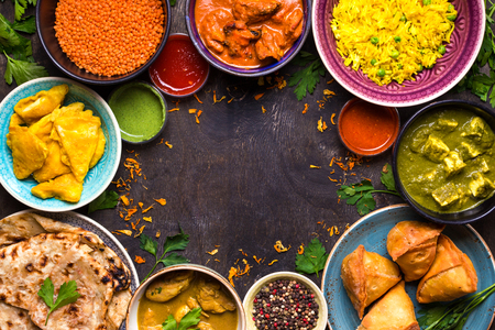 Photo for Assorted indian food on dark wooden background. Dishes of indian cuisine. Curry, butter chicken, rice, lentils, paneer, samosa, naan, chutney, spices. Space for text. Bowls and plates with indian food - Royalty Free Image