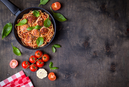 Photo pour Spaghetti with meatballs, tomato sauce. Background. Italian American dish. Meatballs pasta in a pan. Space for text. Overhead. Traditional Italian cuisine. Dark rustic wooden table. Dinner with pasta - image libre de droit